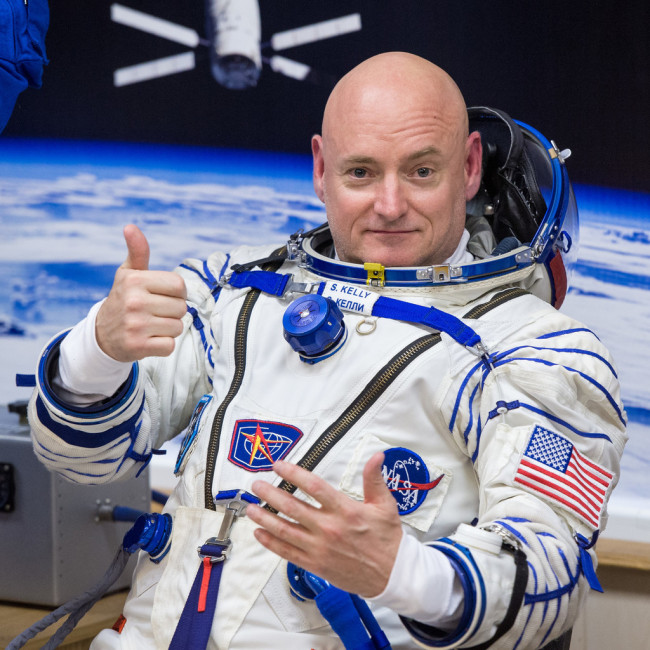NASA Astronaut Scott Kelly gives a thumbs as he and his fellow crew members, Russian Cosmonauts Gennady Padalka, and Mikhail Kornienko of the Russian Federal Space Agency (Roscosmos) have their Russian sokol suits pressure checked ahead of their launch onboard the Soyuz TMA-16M spacecraft to the International Space Station Friday, March 27, 2015 in Baikonor, Kazakhstan. [Photo: IC]