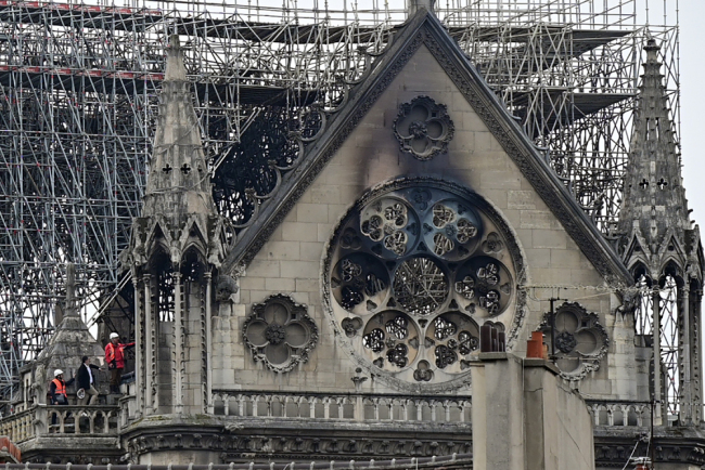 Inspectors are seen on the roof of the landmark Notre-Dame Cathedral in central Paris on April 16, 2019, the day after a fire ripped through its main roof. [Photo: AFP]