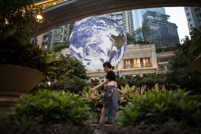 A woman walks past British artist Luke Jerram's giant earth installation in Hong Kong, China, May 2, 2019. [Photo: IC]