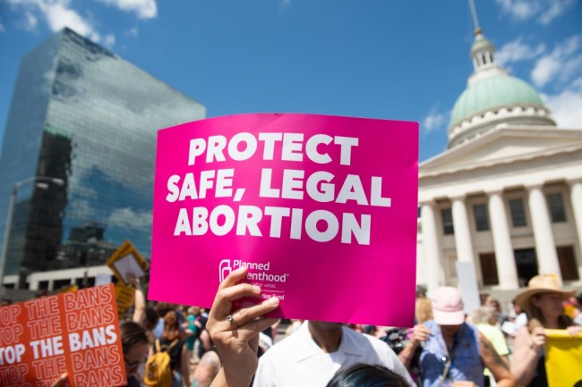 Protesters hold signs as they rally in support of Planned Parenthood and pro-choice and to protest a state decision that would effectively halt abortions by revoking the center's license to perform the procedure, near the Old Courthouse in St. Louis, Missouri, May 30, 2019. [Photo: AFP]