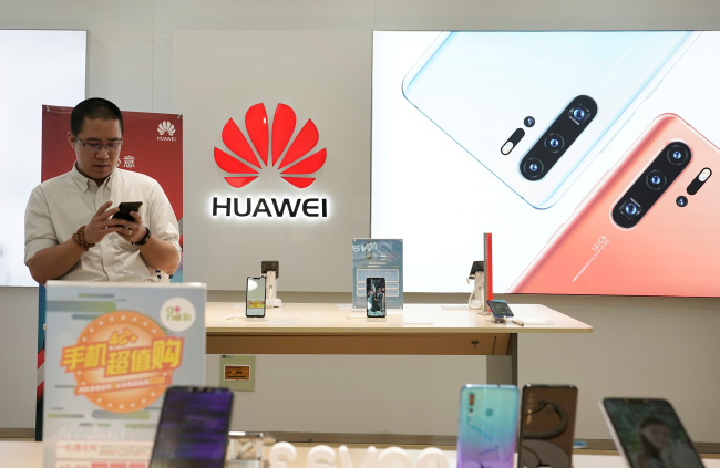 A customer waits to buy a new Huawei P30 smartphone before Huawei's P30 and P30 Pro go on sale at a Huawei store in Beijing, China, April 11, 2019. [Photo: VCG]