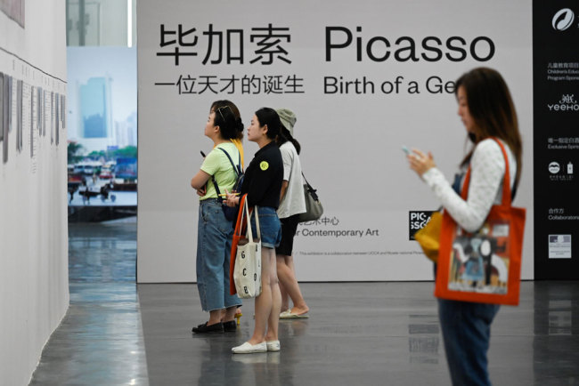 """This picture taken on June 14, 2019 shows people visiting an exhibition named """"Picasso Birth of a Genius"""" at an art gallery in Beijing. [Photo: AFP/Wang Zhao]"""