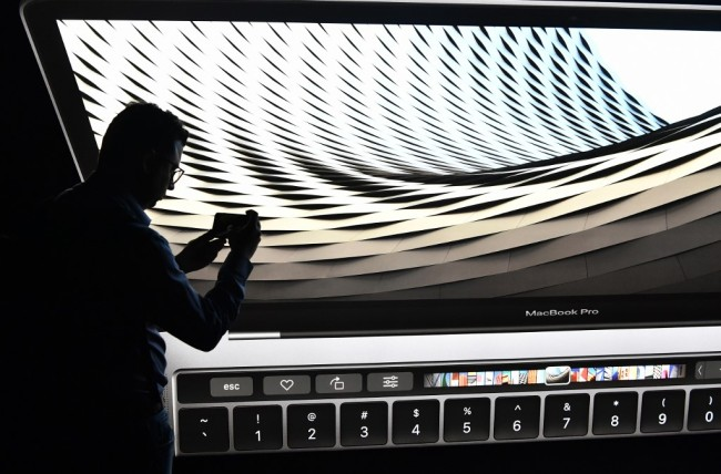 A member of the media walks by a display advertising the new MacBook Pro computer during a product launch event at Apple headquarters in Cupertino, California on October 27, 2016. [Photo: AFP]<br><br>