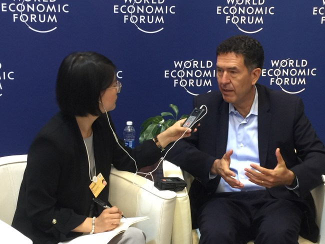 Murat Sonmez, right, speaks to a reporter on the sidelines of the Summer Davos forum in Dalian. [Photo: China Plus]