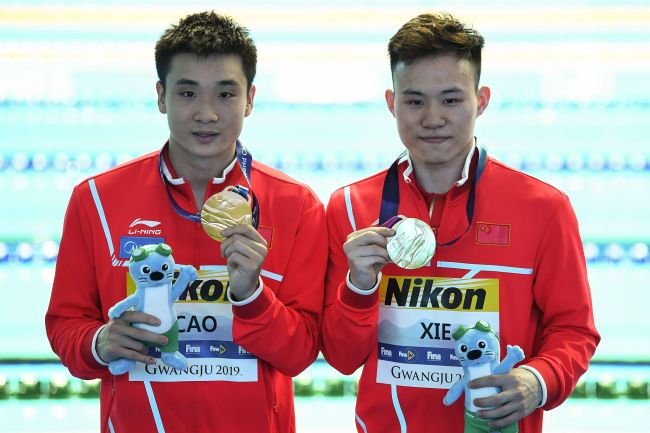 Gold medallist China's Cao Yuan and China's Xie Siyi celebrate during the medals ceremony of the men's synchronised 3m springboard diving event during the 2019 World Championships at Nambu International Aquatics Centre in Gwangju on July 13, 2019. [Photo: VCG/AFP/Manan Vatsyayana]