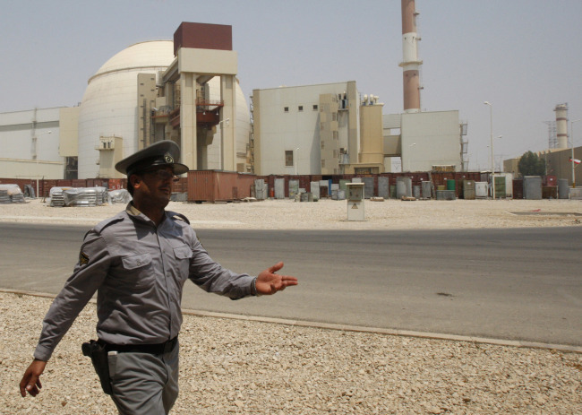 An Iranian security official directs media at the Bushehr nuclear power plant, with the reactor building seen in the background, just outside the southern city of Bushehr, Iran. [File photo: IC]