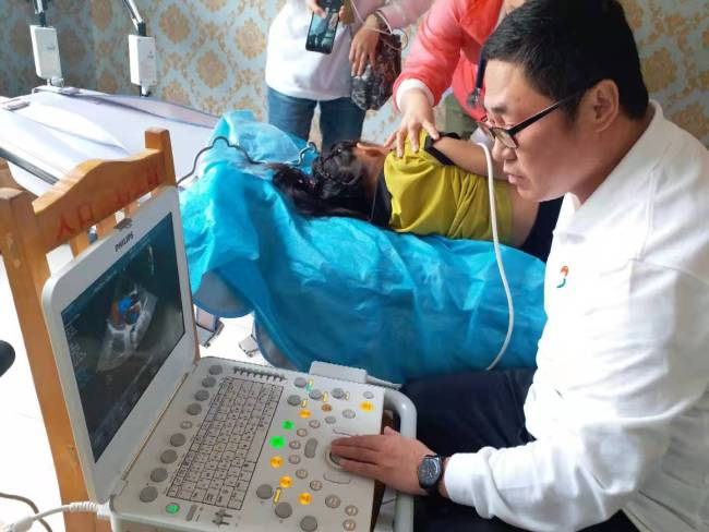 Zhu Shuangli was doing ultrasound for a local boy to check if he had congenital heart disease. [Photo: from China Plus]