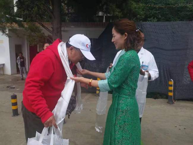 A representative from Tuoding Township presents hada, a white silk scarf, to a voluntary doctor to show respect and blessings. [Photo: China Plus]