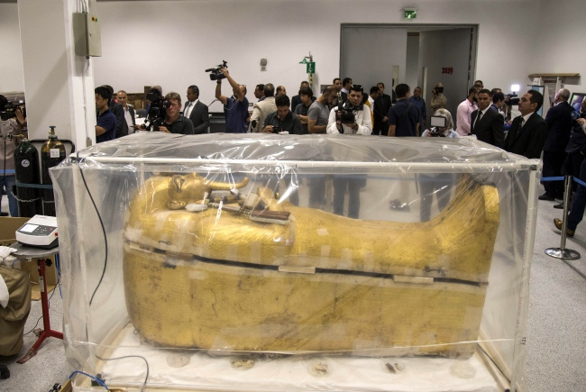 Reporters stand around the gilded coffin of King Tutankhamun that is undergoing a restoration process at the Grand Egyptian Museum in Giza, Egypt, 04 August 2019. [Photo: EPA via IC/Mohamed Hossam]