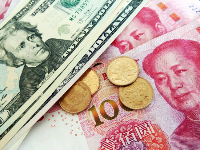 Chinese currency yuan and the U.S. dollars. [File Photo: IC]