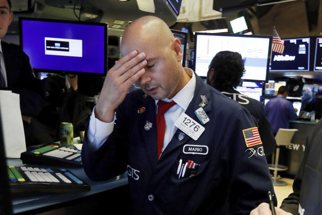 Specialist Mario Picone works on the floor of the New York Stock Exchange, Wednesday, Aug. 14, 2019. The Dow Jones Industrial Average sank 800 points after the bond market flashed a warning sign about a possible recession for the first time since 2007. [Photo: AP/Richard Drew]