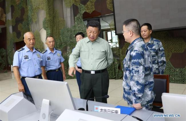 Chinese President Xi Jinping, also general secretary of the Communist Party of China Central Committee and chairman of the Central Military Commission, talks with military officials when inspecting an air force base in Gansu Province on August 22, 2019. [Photo: Xinhua/Li Gang]