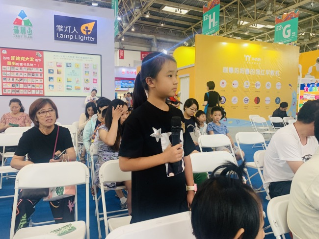 A girl reader asks a question to Lion Cub author Liu Hu during a book promoting engagement. [Photo provided to China Plus]