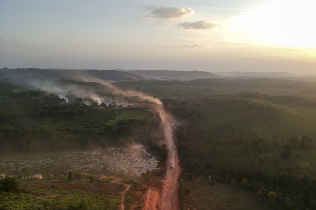 """In this aerial view the red dust of the BR230 highway, known as """"Transamazonica"""", mixes with fires at sunset in the agriculture town of Ruropolis, Para state, northen Brazil, on September 6, 2019. [Photo: AFP/Johannes MYBURGH]"""