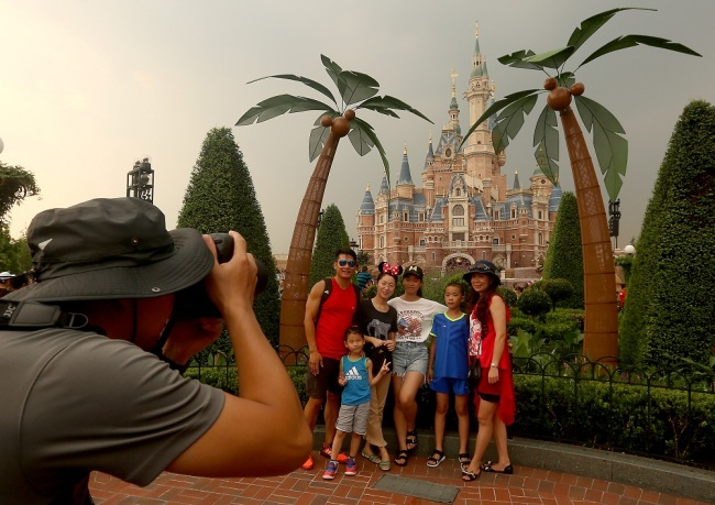 Tourists take group photo in front of the Disney castle in Shanghai Disneyland Resort. [File Photo: UPI via IC/Stephen Shaver]
