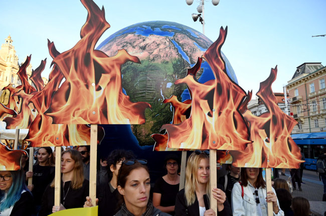 Students and activists hold up a globe as they take part during the Global Climate Strike march downtown Zagreb, Croatia, on September 20, 2019. [Photo: AFP/Denis Lovrovic]