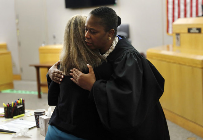 State District Judge Tammy Kemp gives former Dallas Police Officer Amber Guyger a hug before Guyger leaves for jail, Wednesday, Oct. 2, 2019, in Dallas. [Photo: AP]