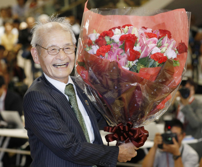 Akira Yoshino of Asahi Kasei Corporation poses with a bouquet of flowers in Tokyo Wednesday, Oct. 9, 2019, following an announcement that he was awarded the Nobel Prize in Chemistry. [Photo: Kyodo News via AP/Yuta Omori]