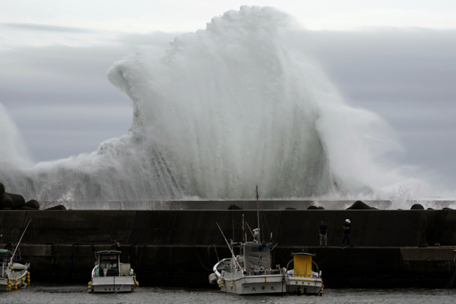 Men look at fishing boats as surging waves hit against the breakwater while Typhoon Hagibis approaches at a port in town of Kiho, Mie Prefecture, Japan, on Friday, Oct. 11, 2019. [Photo: AP/Toru Hanai]