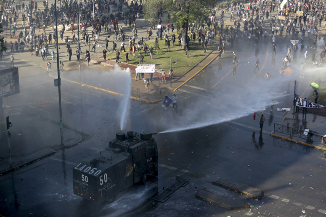 A police truck sprays water canons at protesters, amid ongoing demonstrations triggered by an increase in subway fares in Santiago, Chile, Monday, Oct. 21, 2019. [Photo: AP/Miguel Arenas]