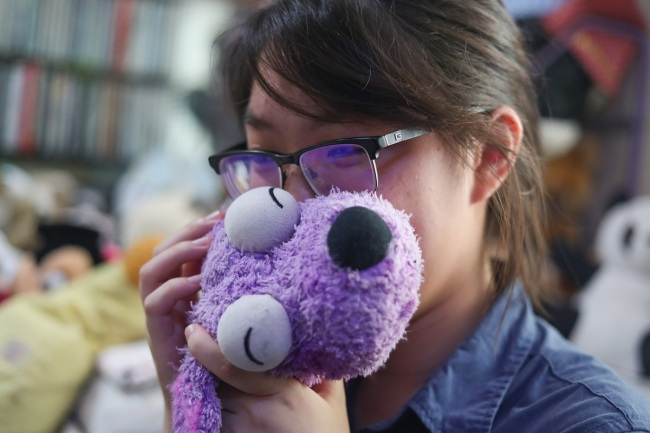 A young woman has a moment with her toy before leaving it at the toy hospital in Shanghai. [Photo: IC]