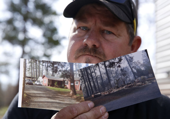 In this Thursday Oct. 24, 2019, photo, Bill Husa displays before-and-after photos of his home lost in last year's Camp Fire in Paradise, Calif. [Photo: AP]