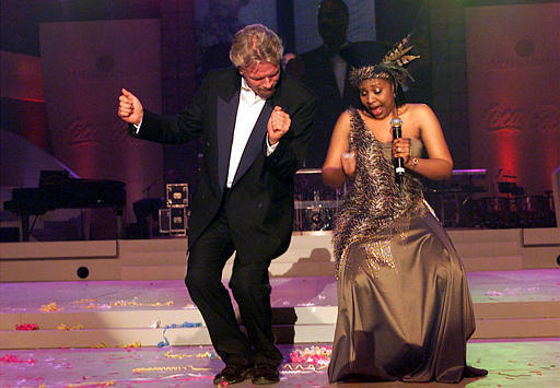 Britain's Sir Richard Branson, left, dances with local star Yvonne Chaka Chaka, at former South African President Nelson Mandela's 85th birthday party celebration in Johannesburg, Saturday July 19, 2003. [File Photo: AP]
