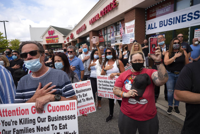 A crowd gives the Pledge of Allegiance while supporting Bobby Catone, the owner of a Staten Island tanning salon, May 28, 2020, in New York. [Photo: AP/Mark Lennihan]