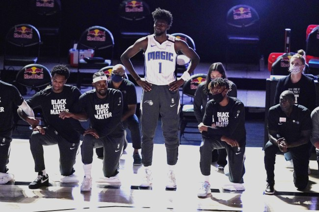Orlando Magic's Jonathan Isaac (1) stands as others kneel before the start of an NBA basketball game between the Brooklyn Nets and the Orlando Magic Friday, July 31, 2020, in Lake Buena Vista, Fla. [Photo: AP]