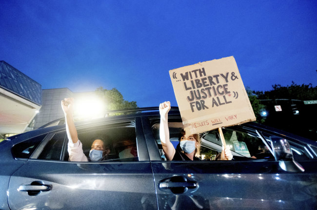 Bobbi Snethen, right, holds a sign during a protest caravan for Black Lives Matter on Friday, July 31, 2020, in Portland, Ore. Following an agreement between Democratic Gov. Kate Brown and the Trump administration to reduce federal officers in the city, nightly protests remained largely peaceful without major confrontations between demonstrators and officers. [Photo: AP]