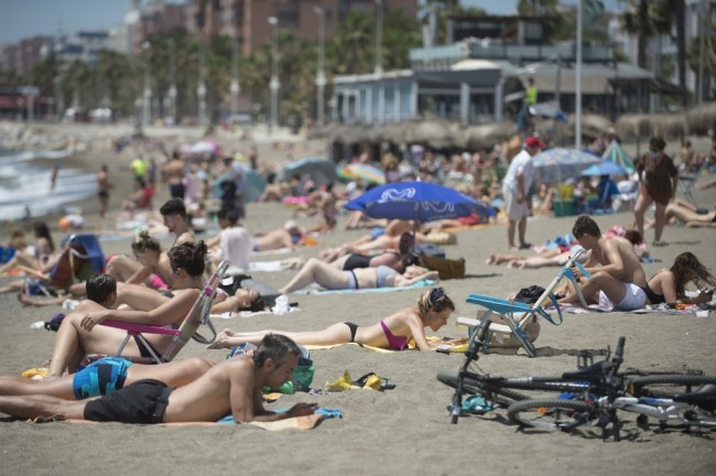 People sunbathe at La Misericordia Beach in Malaga on June 7, 2020, as lockdown measures are eased during the coronavirus COVID-19 pandemic. [File Photo: AFP]